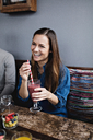 Smiling young woman having drink while sitting at table in restaurant - MASF07550