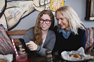 Smiling daughter showing smart phone to woman while sitting at dining table - MASF07559