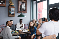 Owner photographing smiling friends through mobile phone at table in restaurant - MASF07562