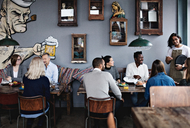 Owner talking to multi-ethnic friends while family having brunch at table in restaurant - MASF07568