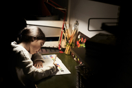 High angle view of girl studying while sitting at illuminated desk in darkroom - MASF07580