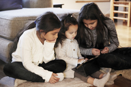 Sisters watching digital tablet while sitting on carpet at home - MASF07601