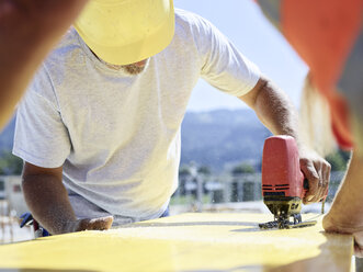 Construction worker cutting plywood with jigsaw on construction site - CVF00336