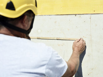 Construction worker using folding ruler and pencil on concrete wall - CVF00342
