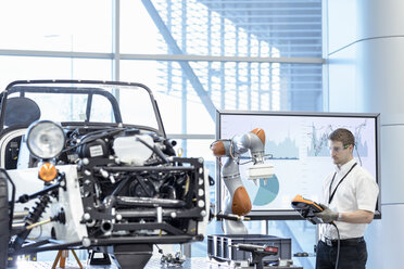 Engineer and robot assembling car in robotics research facility - CUF00035