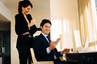 Businessman and businesswoman sharing text message in hotel room - CUF00047