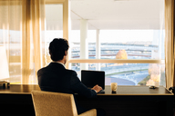 Businessman using laptop and looking out of hotel bedroom window - CUF00065