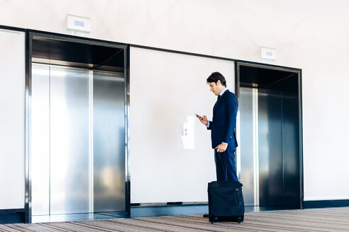 Businessman with wheeled luggage by hotel lift - CUF00083