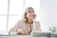 Smiling mature businesswoman at desk looking up - HHLMF00243