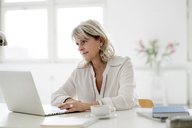 Smiling mature businesswoman working on laptop at desk - HHLMF00246