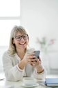 Laughing mature businesswoman looking at cell phone at desk - HHLMF00249