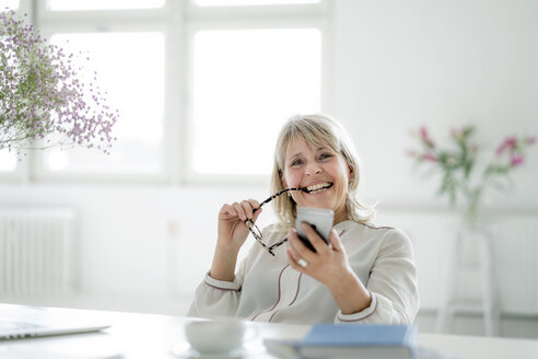 Portrait of happy mature businesswoman holding cell phone at desk - HHLMF00252