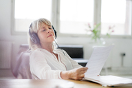 Relaxed mature businesswoman wearing headphones at desk - HHLMF00255