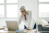 Mature businesswoman working on laptop at desk - HHLMF00258