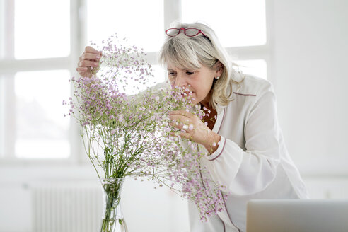 Mature woman with laptop caring for flowers - HHLMF00261