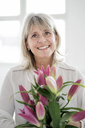 Portrait of smiling mature woman holding bunch of flowers - HHLMF00264