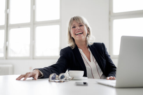 Portrait of laughing mature businesswoman with laptop at desk in the office - HHLMF00273
