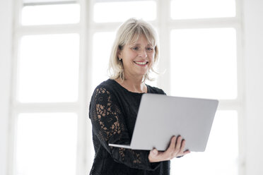 Smiling mature woman holding laptop - HHLMF00282
