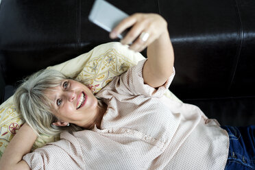 Happy mature woman lying down holding cell phone - HHLMF00285