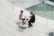 Young businesswoman and man meeting at sidewalk cafe, high angle view - ISF00001