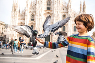 Boy feeding pigeons in Milan Cathedral square, Milan, Lombardy, Italy - ISF00031