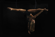 Young female aerial acrobat doing splits hanging upside down from hoop, black background - ISF00040