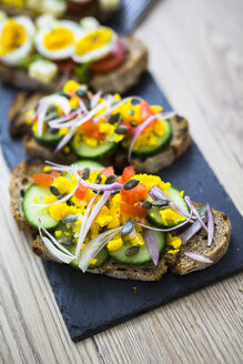 Vegetarian breakfast with bread, eggs and cucumber slices on slate - GIOF03935
