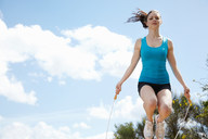 Woman jumping rope outdoors - CUF00401