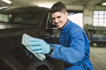 Smiling man cleaning a car in a workshop - RAEF01996