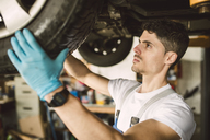 Mechanic working on the underbody of a car in a workshop - RAEF02011
