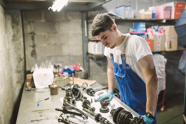 Mechanic overwhelmed by the parts of a car in a workshop - RAEF02017 - Ramon Espelt/Westend61