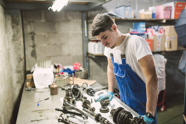 Mechanic overwhelmed by the parts of a car in a workshop - RAEF02017