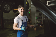 Portrait of smiling mechanic in his workshop - RAEF02020