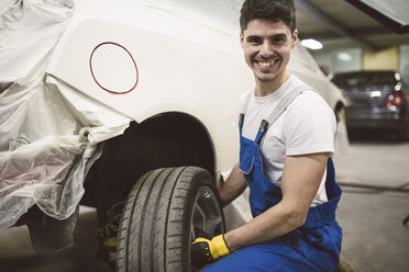 Portrait of smiling mechanic changing car tyre in his workshop - RAEF02023