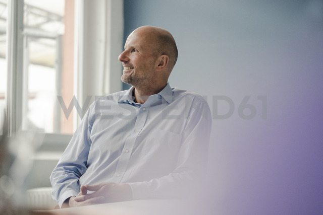 Smiling mature businessman looking out of window - KNSF03805