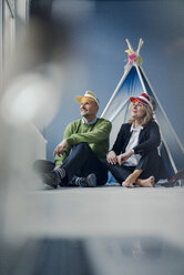 Smiling couple wearing sun visors sitting at teepee indoors - KNSF03820