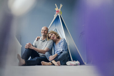 Smiling couple sitting at teepee indoors - KNSF03823
