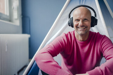 Portrait of smiling mature man wearing headphones sitting at teepee indoors - KNSF03826