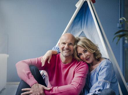 Portrait of smiling couple at teepee indoors - KNSF03829