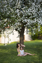 Two girls sitting in front of blossoming apple tree in the garden - LVF06929
