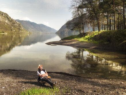 Italy, Lombardy, senior man relaxing at Lake Idro - LAF02015