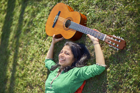 Happy young woman with guitar lying on meadow - BEF00020