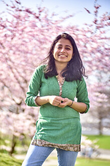 Portrait of happy young woman in a park at cherry blossom tree - BEF00023