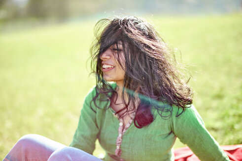Happy young woman with windswept hair on a meadow - BEF00026