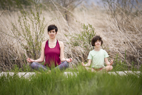 Mother and daughter doing yoga on boardwalk - JSMF00177
