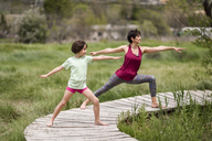 Mother and daughter doing yoga on boardwalk - JSMF00180