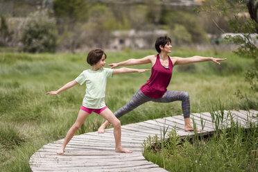 Mother and daughter doing yoga on boardwalk - JSMF00180