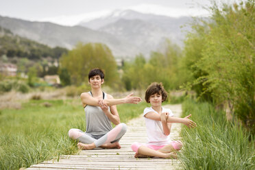 Mother and daughter doing yoga on boardwalk - JSMF00183