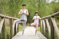Mother and daughter doing yoga on boardwalk - JSMF00186
