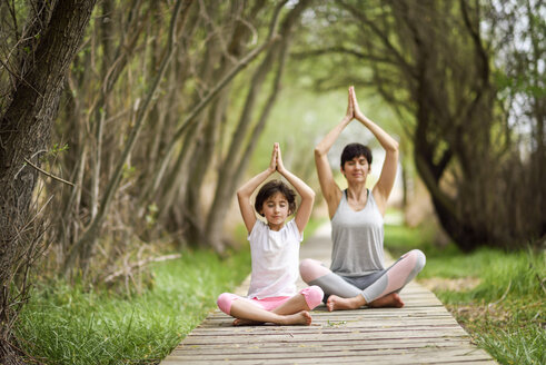 Mother and daughter doing yoga on boardwalk - JSMF00189